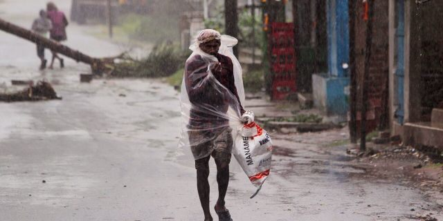 A man covers himself with a plastic sheet and walks in the rain ahead of Cyclone Amphan landfall, at Bhadrak district, in the eastern Indian state of Orissa, May 20, 2020.