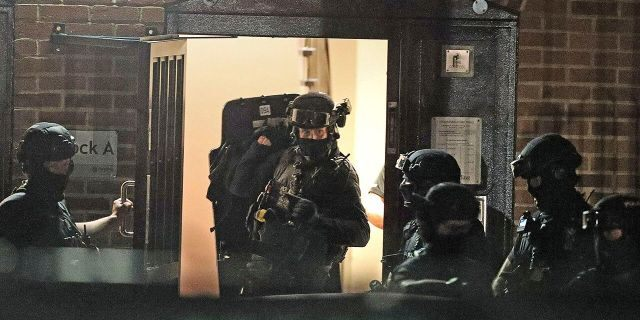 """Armed police officers work at a block of flats off Basingstoke Road in Reading after an incident at Forbury Gardens park in Reading, England, Saturday, June 20, 2020. Several people were injured in a stabbing attack on Saturday, and British media said police were treating it as """"terrorism-related."""" (Steve Parsons/PA via AP)"""