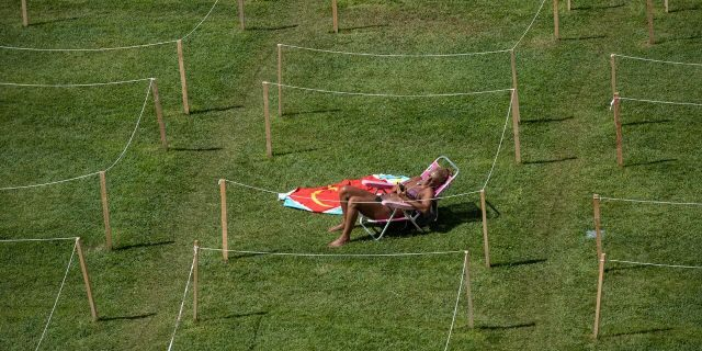 A sunbather checks her smartphone on a hot day of summer in Rivas Vaciamadrid, Spain, Wednesday, July 29, 2020.