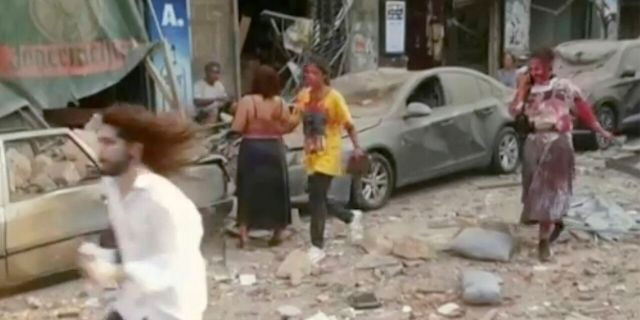 In this frame from video people walk down the street after an explosion in Beirut, Tuesday, Aug. 4, 2020. Explosions rocked Beirut, inflicting many injuries and damaging buildings in a large radius around the city's port. (AP Photo)