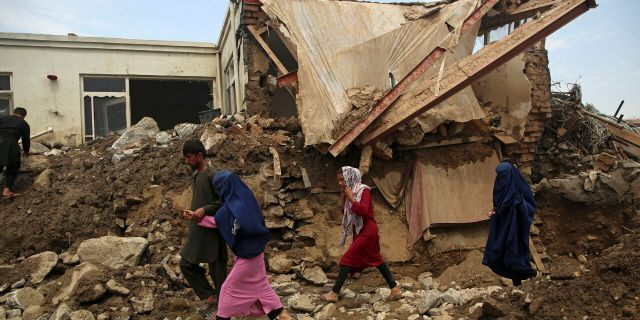 Afghan family walk near to the damaged houses after after a mudslide during heavy flooding in the Parwan province, north of Kabul, Afghanistan, Wednesday, Aug. 26, 2020.