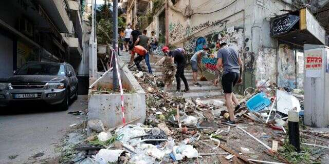 People clean up after a massive explosion in Beirut, Lebanon, Wednesday, Aug. 5, 2020.