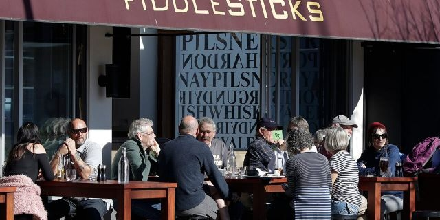Customers at a cafe enjoy lunch in the sunshine in Christchurch, New Zealand, Sunday, Aug. 9, 2020. New Zealand marked a 100 days of being free from the coronavirus in its communities Sunday, Aug. 9, with just a handful of infections continuing to be picked up at the border where people are quarantined. (AP Photo/Mark Baker)