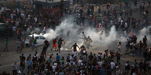 Demonstrators run away from tear gas fired by riot police during a protest following Tuesday's blast, in Beirut, Lebanon August 8, 2020. REUTERS/Hannah McKay - RC2S9I91Y6H3