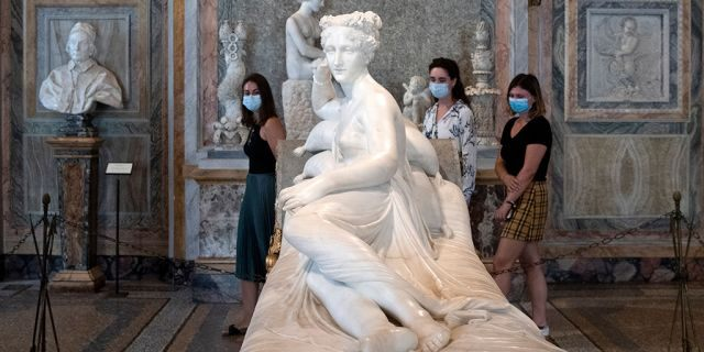 "Visitors wearing a face mask view ""Paolina Borghese Bonaparte as Venus Victrix"", an 1805-1808 marble sculpture by Antonio Canova at the Galleria Borghese museum in Rome on May 19, 2020. (Photo by Tiziana FABI / AFP) (Photo by TIZIANA FABI/AFP via Getty Images)"