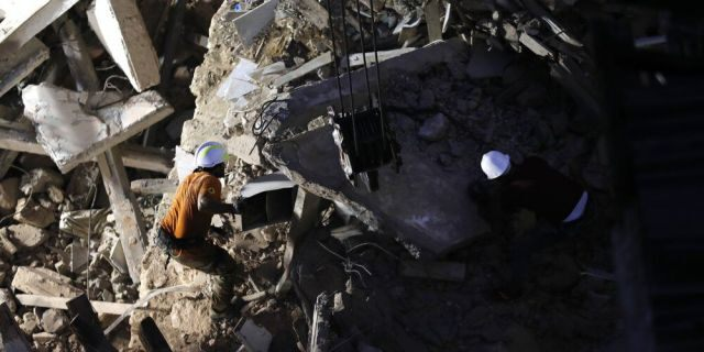 Lebanese and Chilean rescuers searching in the rubble of a collapsed building after getting signals there may be a survivor under the rubble in Beirut, Lebanon, early Friday, Sept. 4, 2020. A pulsing signal was detected Thursday from under the rubble of a Beirut building that collapsed during the horrific port explosion in the Lebanese capital last month, raising hopes there may be a survivor still buried there. (AP Photo/Hussein Malla)