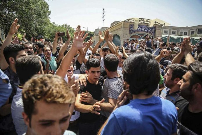FILE - In this June 25, 2018 file photo, a group of protesters chant slogans at the main gate of the Old Grand Bazaar, in Tehran, Iran. On Saturday, Sept. 5, 2020, Iran broadcast the televised confession of a wrestler facing the death penalty after a tweet from President Donald Trump criticizing the case, a segment that resembled hundreds of other suspected coerced confessions aired over the last decade in the Islamic Republic. The case of 27-year-old Navid Afkari has drawn the attention of a social media campaign that portrays him and his brothers as victims targeted over participating in protests against Iran's Shiite theocracy in 2018. (Iranian Labor News Agency via AP, File) Photo: AP / Iranian Labor News Agency, ILNA