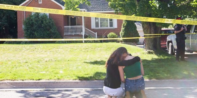 Two women kneel outside the Oshawa, Ontario, house where a shooting left five people dead and one wounded, Sept. 4, 2020. (Getty Images)