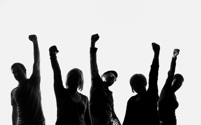 Five silhouettes of people standing in a row and raising their hands. Studio shot on the white background.