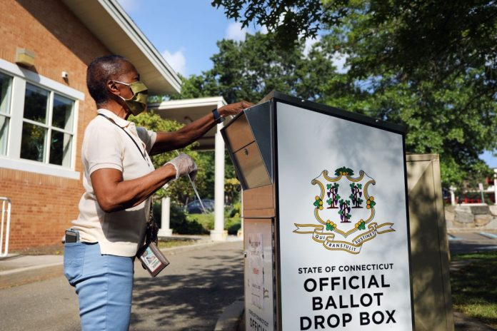 STAMFORD, CONNECTICUT - AUGUST 11: A woman drops her Connecticut 2020 presidential primary ballot at a secure ballot drop box at a Stamford library on August 11, 2020 in Stamford, Connecticut. Due to the ongoing COVID-19 pandemic, Connecticut Governor Ned Lamont signed an executive order allowing all registered voters to vote absentee in the August 11, 2020 primary. Connecticut has also experienced fallout from the recent tropical storm, which knocked out power to half of the state at its peak. President Trump has been critical of the absentee ballot process saying it contributes to voter fraud.  (Photo by Spencer Platt/Getty Images)