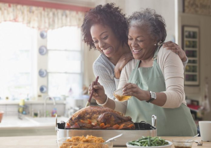 A mother and daughter looking happy while standing over a Thanksgiving turkey