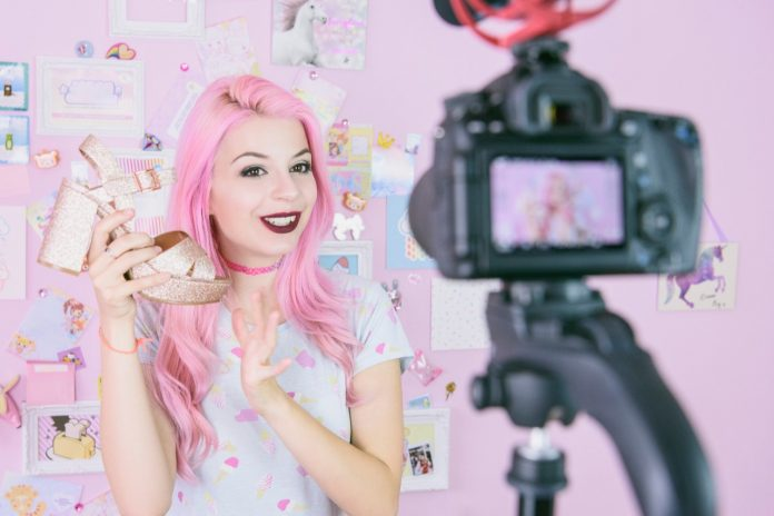 Social media influencer reviewing footwear, she is vlogging about women's fashion and filming herself at home on a video camera