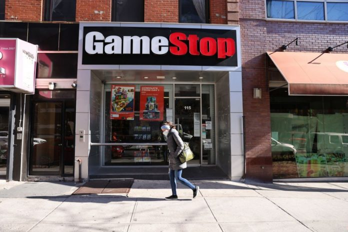NEW YORK, NEW YORK - JANUARY 28: People walk by a GameStop store in Brooklyn on January 28, 2021 in New York City. Markets continue a volatile streak with the Dow Jones Industrial Average rising over 500 points in morning trading following yesterdays losses. Shares of the video game retailer GameStop plunged. (Photo by Spencer Platt/Getty Images)