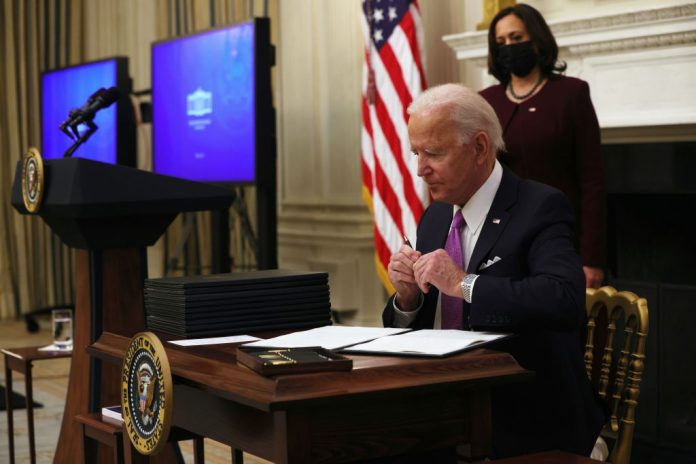 WASHINGTON, DC - JANUARY 21: U.S. President Joe Biden signs executive orders as Vice President Kamala Harris looks on during an event at the State Dining Room of the White House January 21, 2021 in Washington, DC. President Biden delivered remarks on his administrationâ  s COVID-19 response, and signed executive orders and other presidential actions. (Photo by Alex Wong/Getty Images)