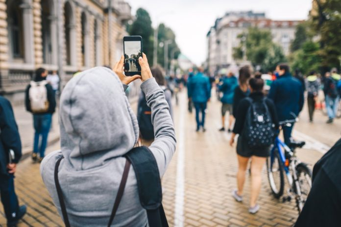 Person with a hood, recording video / taking a photo of a crowd of people.