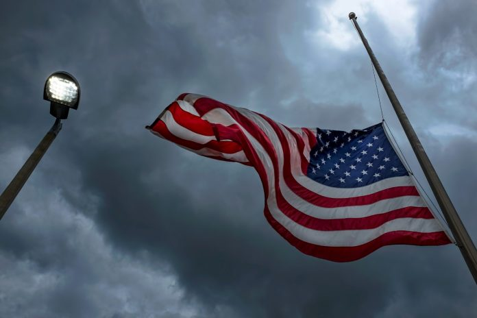 American flag at half-mast on a pole near a glowing street light in Clearwater, Florida during a storm.