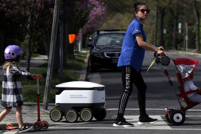 WASHINGTON, DC - APRIL 08:  A Starship Technologies delivery robot crosses a street as local residents pass by April 8, 2020 in the Chevy Chase neighborhood of Washington, DC. The local Broad Branch Market is teaming up with Starship to provide delivery service of groceries and prepared food by autonomous robots to neighboring areas amid the COVID-19 pandemic. (Photo by Alex Wong/Getty Images)