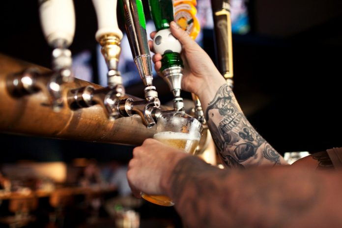 tattooed-bartender-pouring-beer-alcohol