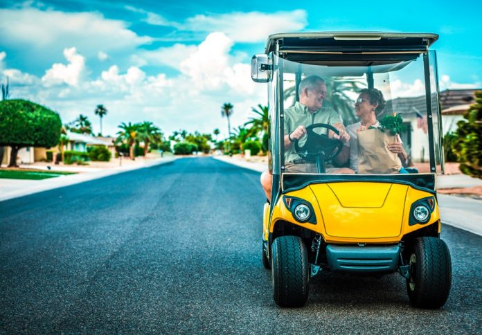 an older husband and wife driving a golf cart on a subdivision street taking their groceries home