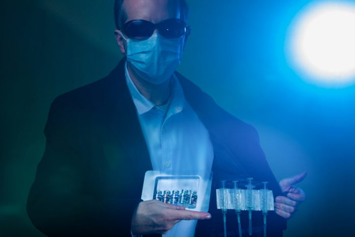 """Suspicious man in suit, wearing a surgical protective face mask and sunglasses. Deals in fake illegal  COVID-19 (SARS-CoV-2) Coronavirus vaccine vials and injection syringes. Opens jacket and shows hidden syringes and a box of vaccine bottles.Note: QR code on bottles was generated by me and contains generic text: """"SARS-CoV-2 Vaccine"""""""